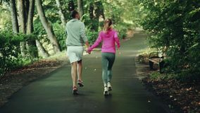 A girl and a man are engaged in a sport. In a park stock video footage