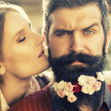 Girl and man with flowers on beard Royalty Free Stock Image
