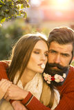 Girl and man with flowers on beard. Young beautiful embracing couple of women and men with long black beard with many little white red and pink flowers sunny day stock images