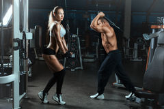 Girl and  man go sports hall with machines for bodybuilders. Stock Photos