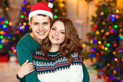 A girl and a man in a hat Santa in a green dress embrace on a ba. A girl and a men in a hat Santa in a green dress embrace on a background of bright Christmas Stock Photo
