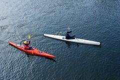 Girl and man paddles a kayak on the river. Man and women paddles a white and red kayak on the river near the shore, kayaking Royalty Free Stock Photos