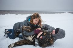 Girl and man is playing with dog in snow, Happy holidays, love moments and rest in nature in winter. Girl and men is playing with dog in snow, Happy holidays Royalty Free Stock Photos