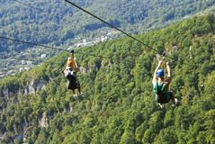 Girl and man ride on the attraction. SOCHI, RUSSIA - SEPTEMBER 19, 2017: Girl and man ride on the attraction `ZipLine` in Ahshtyrsky gorge Stock Photography