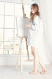 Girl in a man's shirt near the easel. Houses window Royalty Free Stock Photos