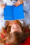Girl in a man's shirt is reading book Stock Photo