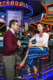 Girl and man in 60s style. Girl dressed in 60s style sits at the bar in the company of her boyfriend Royalty Free Stock Images