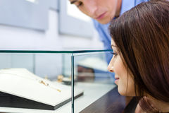 Girl with man selects expensive jewelry. Girl with men selects expensive jewelry at jeweler's shop. Concept of wealth and luxurious life Stock Photography