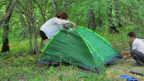 The girl and the man set the tent in the deciduous stock video footage