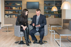 A girl and a man sitting with notepad Royalty Free Stock Image