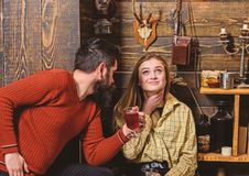 Girl and man on smiling faces enjoy cozy atmosphere with hot drinks. Couple spend pleasant evening, interior background. Girl and men on smiling faces enjoy cozy stock photography