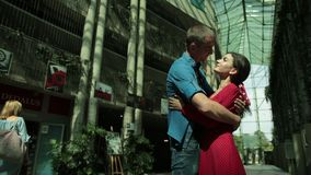 Girl and man tenderly embrace, next to an overgrown house with bushes. Couple in love, brunette girl in red dress and man in blue shirt, tenderly embrace, next stock footage