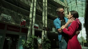 Girl and man tenderly embrace, next to an overgrown house with bushes. Young couple in love, brunette girl in red dress and man in blue shirt, tenderly embrace stock footage