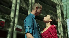 Girl and man tenderly embrace, next to an overgrown house with bushes. Young couple in love, girl in red dress and man in blue shirt, tenderly embrace, next to stock video
