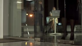 Girl Manager out of the office with glass doors. Slow motion, evening time stock footage