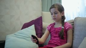 Girl manages remote control tv stock video footage