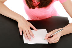Girl with manicured hands writing Stock Images