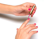 A girl manicures. Macro shot  a picture of female hands putting a varnish on nails Royalty Free Stock Photos