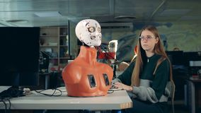 Girl is manipulating robot`s face by means of a computer