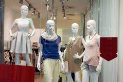 Girl mannequins in shop window. Mannequins Standing In Store Window Display Of Women`s Casual Clothing Shop In Shopping Mall Stock Photos