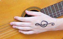 Girl& x27; mano y guitarra de s fotografía de archivo