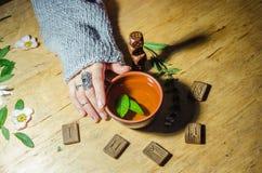 Girl& x27; manos de s, runas y té caliente de la menta Foto de archivo libre de regalías