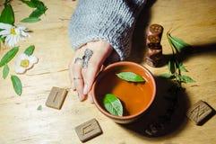 Girl& x27; manos de s, runas y té caliente de la menta Imágenes de archivo libres de regalías
