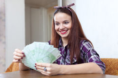 Girl with many euro in home Stock Images