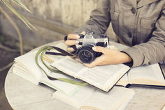 Girl with many open books and old style camera Royalty Free Stock Photography