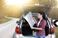 Girl with map behind car Stock Image