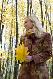 Girl with a maple leaf. Portrait of a girl with a maple leaf in autumn park Stock Images