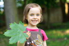Girl with a maple leaf. Portrait of cute little girl with a maple leaf Stock Photography