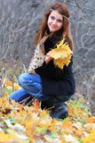 Girl and maple leaves. Young girl with long red hair holding yellow maple leaves outside in the park Stock Image