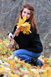 Girl and maple leaves. Young girl with long red hair holding yellow maple leaves outside in the park Stock Photography