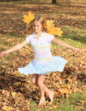 Girl with maple leaves dancing. Barefoot kid - smiling blond girl with long hair decorated with maple leaves dancing in fallen leaves on autumn as nymph Royalty Free Stock Image