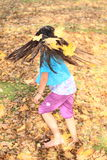 Girl with maple leaves twisting. Barefoot kid - smiling brunette girl with long hair decorated with maple leaves twisting in fallen leaves on autumn Royalty Free Stock Images