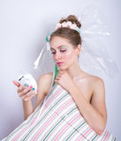 Girl-marshmallow with a pillow and alarm clock in her hands. Stock Image