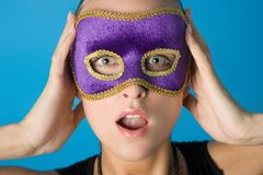 Girl in the mask. Young beautiful model in violet carnival mask. With open mouth and expression of surprise on her face stock images
