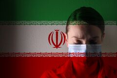 Girl in a mask against the background of the Iran flag, coronavirus, danger and threat, outbreak of a dangerous virus. Photo for