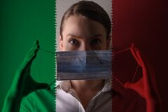 Girl in a mask against the background of the Italy flag, coronavirus, danger and threat, outbreak of a dangerous virus. Photo for