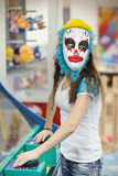 Girl in a mask of a clown at children's parties Royalty Free Stock Photo