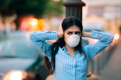 Girl With Mask Covering her Ears Because of Noise Pollution. Worried woman fighting urban pollution with safety measures Royalty Free Stock Photo