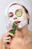 Girl with a mask and cucumber Stock Image