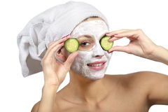 Girl with a mask and cucumber. Beautiful girl with a mask and cucumber slices on his face on a white background royalty free stock photos