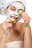 Girl with a mask and cucumber Royalty Free Stock Images