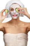 Girl with a mask and cucumber Stock Images