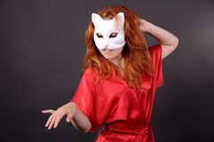 Girl in mask depicting a cat. Girl in a white mask depicting a cat stock photography