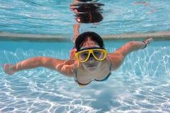 Girl in mask dive in swimming pool stock image