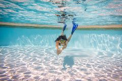 Girl in mask dive in swimming pool royalty free stock photo