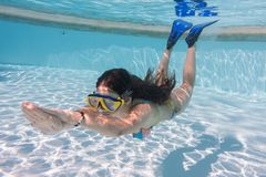 Girl in mask dive in swimming pool royalty free stock photography